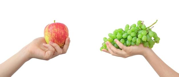 Микс красного яблока и зеленого винограда, фрукты, изолированные на белом фоне, здоровая пища в руке фото
