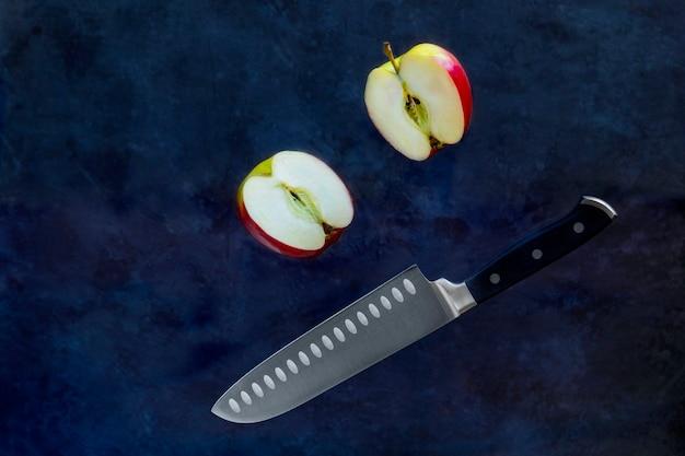Красное яблоко и нож, летящий в воздухе на темном фоне. концепция левитации еды. копировать пространство