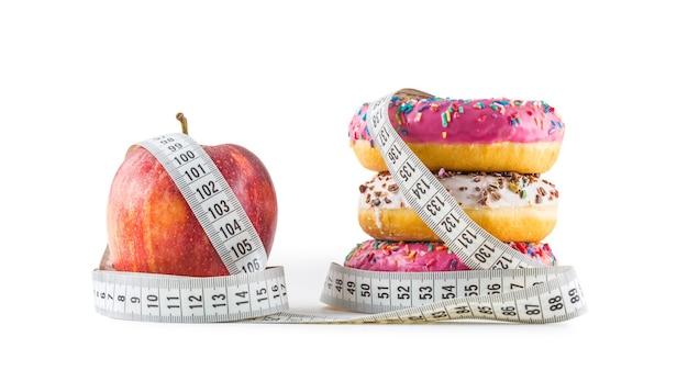 赤リンゴと3つのカラフルなドーナツは、白で隔離された巻尺に包まれています。