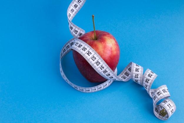 Красное яблоко и белый сантиметр на синем.
