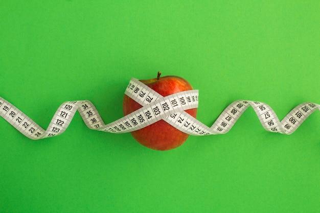 Красное яблоко и белый сантиметр на зеленом фоне