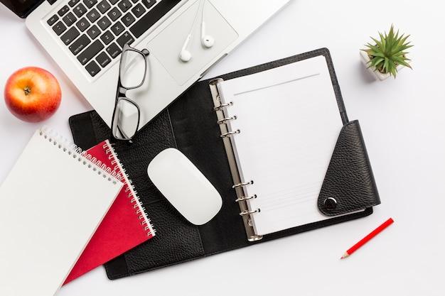 Красное яблоко, дневник, мышь, очки, наушники, карандаш и ноутбук на белом столе