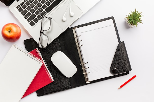 Red apple,diary,mouse,eyeglasses,earphones,pencil and laptop on white desk
