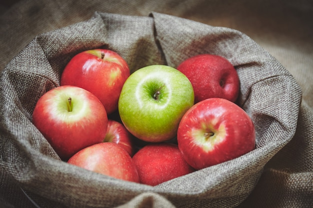 Red apple and green apple in basket with sackcloth background texture