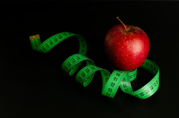 Red apple and green measuring tape on black