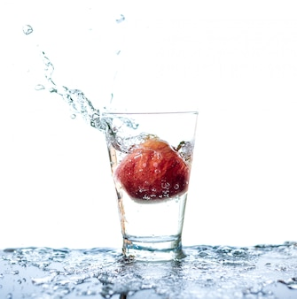 Red apple has droping to the glass and splashing water around the glass and on the table