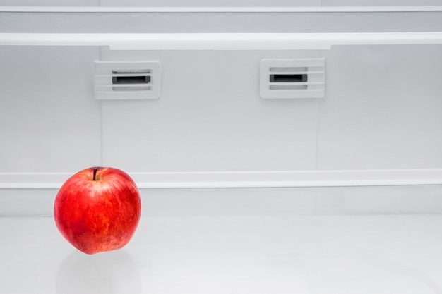 空の冷蔵庫に赤いリンゴ。