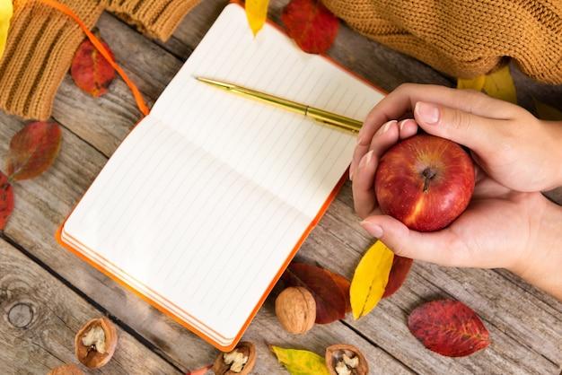 Красное яблоко в руке на поверхности осенней композиции