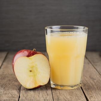 木製のテーブルの上にフルーツとグラスの赤いリンゴジュース