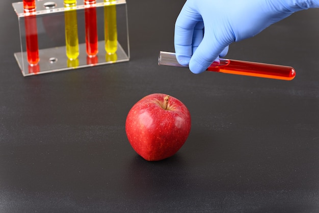 A red apple and laboratory glass with red liquid how the fruit is colored.