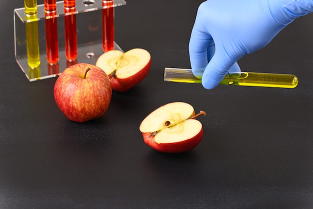 A red apple and laboratory glass with red liquid