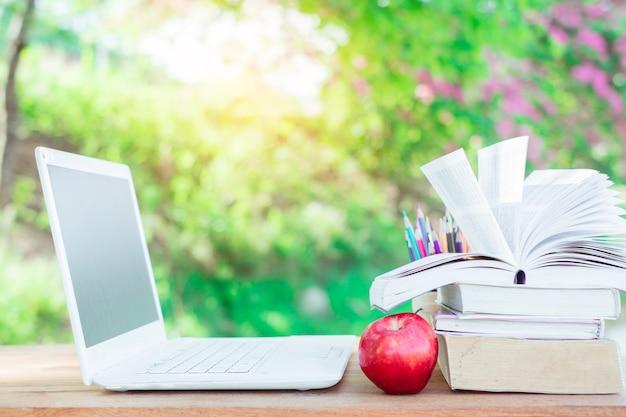 자연 백그라운드에서 나무 테이블에 빨간 사과, 노트북, 책 스택