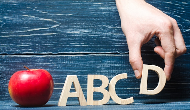Red apple and letters abcd. the hand puts the letter d in the alphabet order