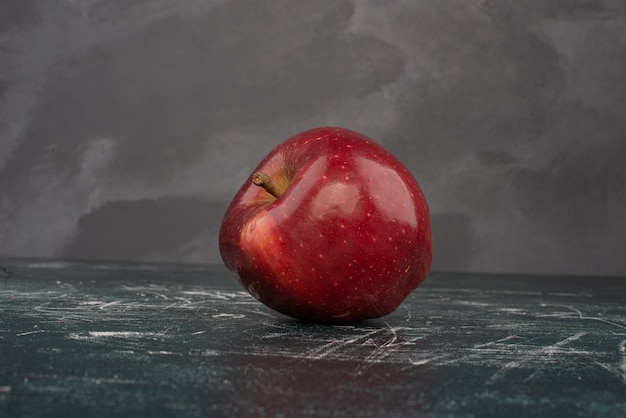 Red apple on marble background .