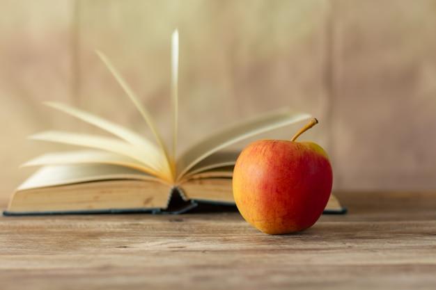 Красное яблоко на размытом фоне стены ретро книги,