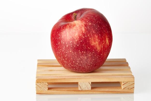 Красное яблоко на логистическом поддоне в ожидании транспортировки к месту назначения