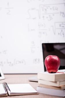 後ろにぼやけたホワイトボードとテーブルの上の本、ノート、鉛筆の山に赤いリンゴ。学校のコンセプト