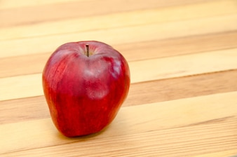 Red apple on wooden table background