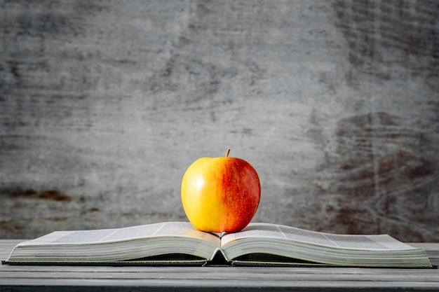 Red apple on open book with wooden background