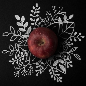 Red apple over outline floral hand drawn