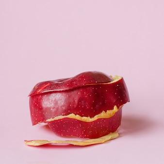 循環経済のリサイクルのシンボルとしてピンクの背景に赤いリンゴの皮