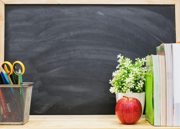 赤いリンゴ、鉛筆、ブラックボードの背景が付いている本、学校のコンセプトに戻る。