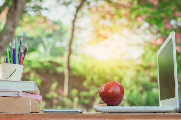 A red apple and pencil sitting on laptop keyboard with school books