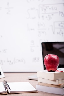 Red apple on pile of books, notebook and pencils on table with a blurred white board in the back. school concept