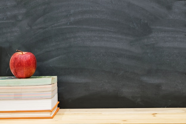 Red apple resting on the book with black board background, back to school concept.