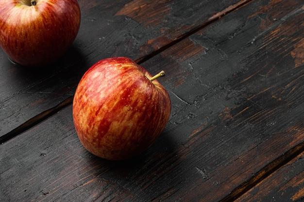 텍스트 복사 공간이 있는 오래된 어두운 나무 테이블 배경에 있는 빨간 사과 세트