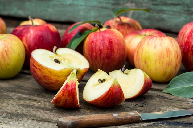 Red apple sliced and knife on old wooden table