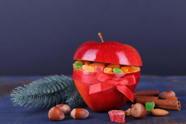 シナモン、モミの木の小枝、色の木製テーブルと暗い背景にヘーゼルナッツとドライフルーツを詰めた赤いリンゴ