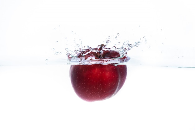 Red apple thrown into the water