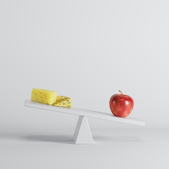 Red apple tipping seesaw with cheese on opposite end on white background.