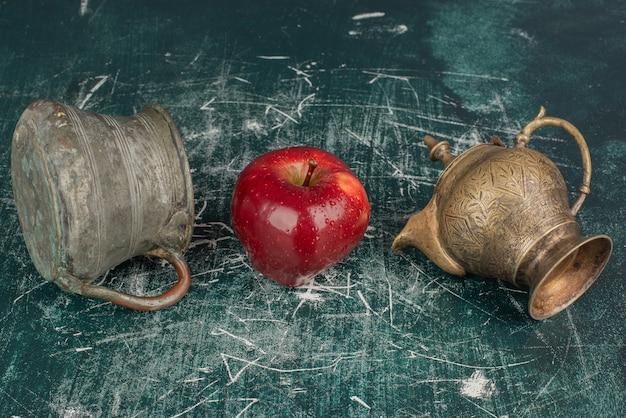 赤いリンゴ、花瓶、大理石のテーブルの上の古典的なティーポット。