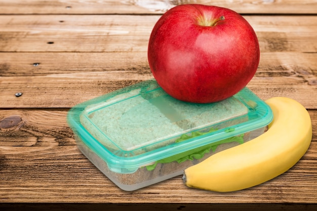 Red apple with banana and food box  for school