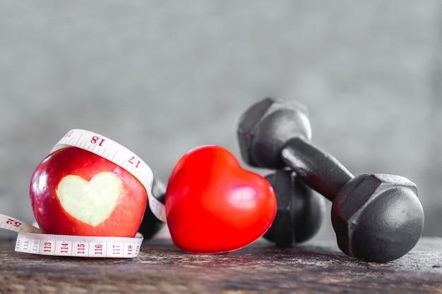 Красное яблоко с гантелями, измерительная лента, спортивная диета и концепция здорового сердца