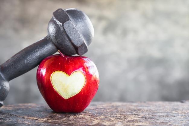 Красное яблоко с гантелями, спортивная диета, концепция здорового сердца