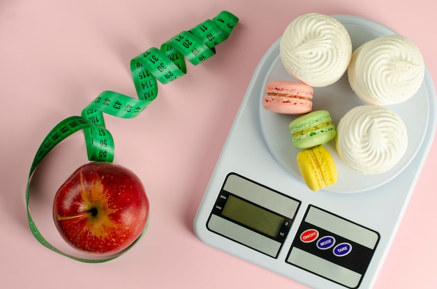 Red apple with green measuring tape, digital kitchen scales with macarons and meringues on pink