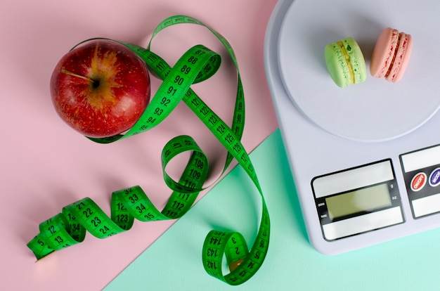 Red apple with green measuring tape, digital kitchen scales with macarons on pink and mint.