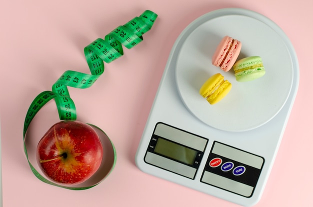 Red apple with green measuring tape, digital kitchen scales with macarons on pink