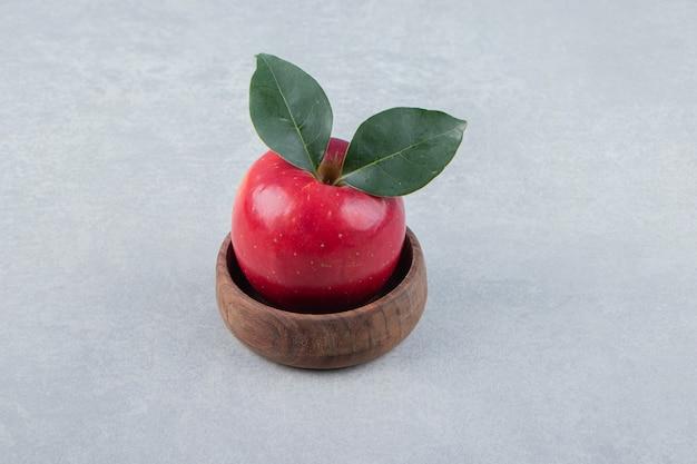 Mela rossa con foglie in ciotola di legno.