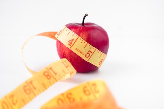 Red apple with measuring tape on table