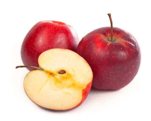 Красное яблоко с ломтиком на белом фоне.