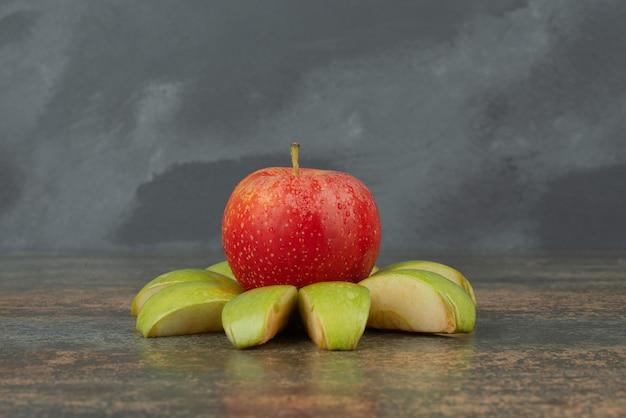 Mela rossa con fettine di mela sulla superficie in marmo.