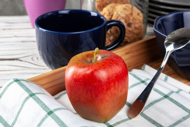 Red apple with tea cup on wooden tray
