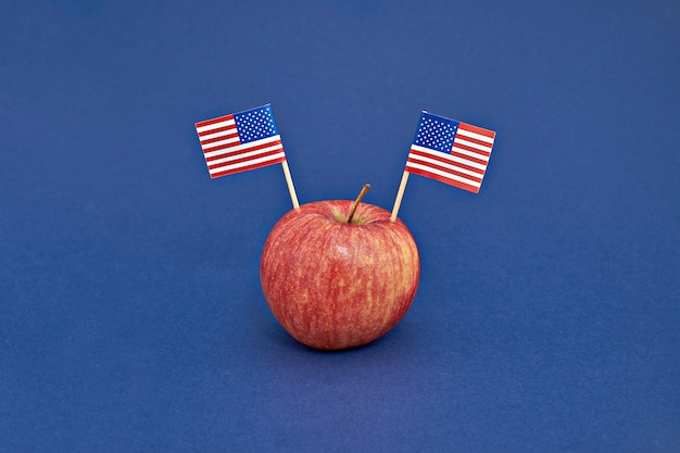 Red apple with two flags of usa on blue background. presidents day of america concept