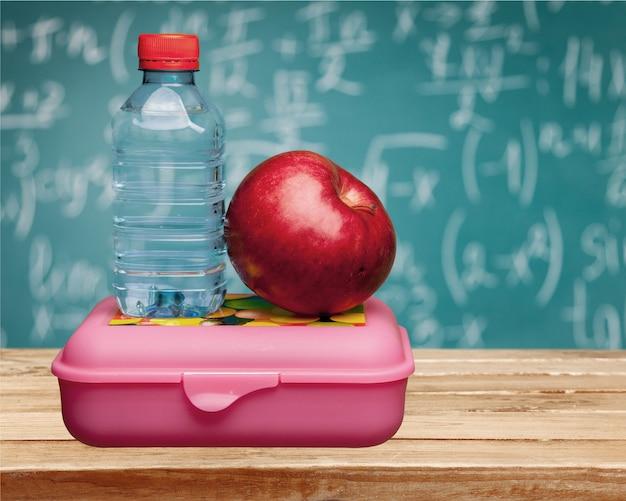学校の机の上に水と食べ物と赤いリンゴ