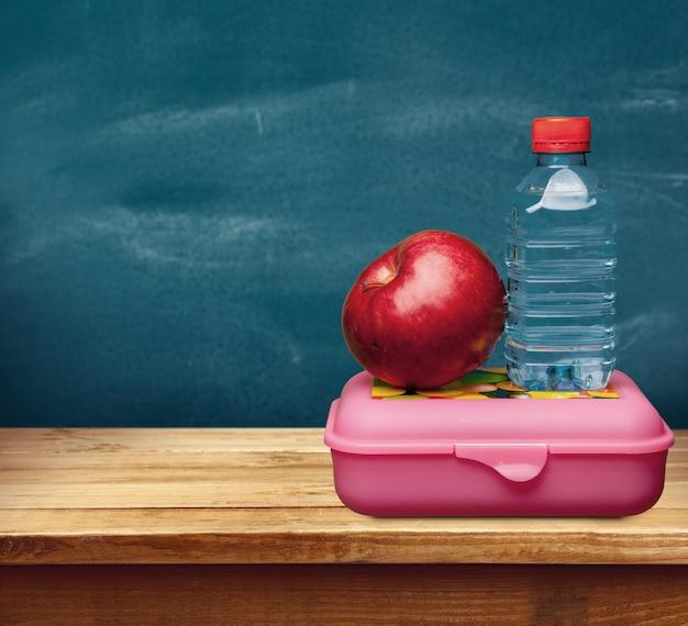 학교 책상에 물과 음식이 있는 빨간 사과