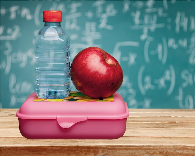 Red apple with water and food on the school desk